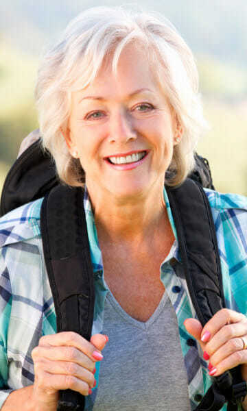 Woman wearing a backpack out walking. Keeping fit reduces the risk of Aneurysms