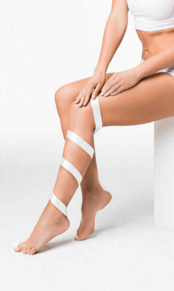 Woman with white ribbon wrapped up a bare leg. Varicose Veins page image