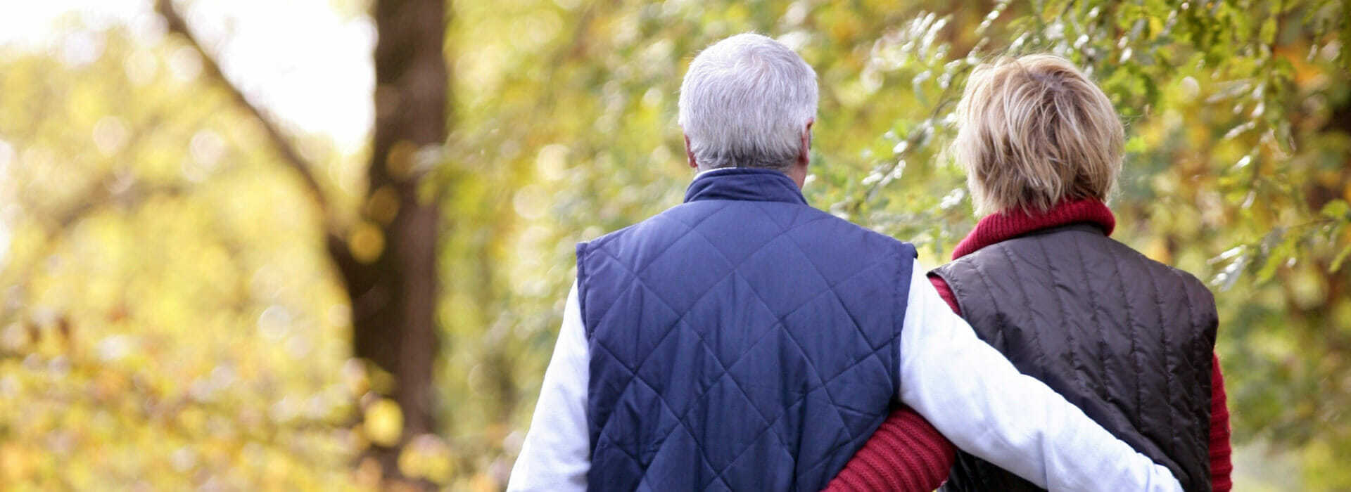 Carotid disease survivor walking down a forest path with their partner.