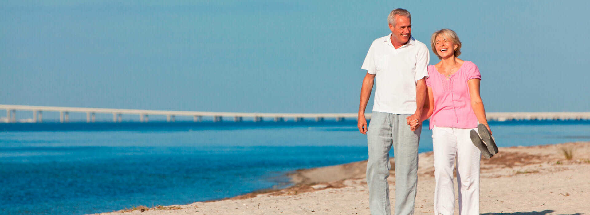 Middle aged couple walking on a sandy beach on the edge of a bay, with a bridge in the background. Healthy veins and blood vessels in elderly people.