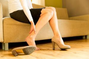 Woman rubs sore leg after taking off shoes